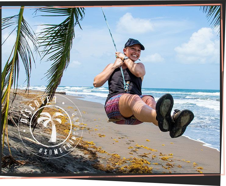 young woman zip lining across the beach