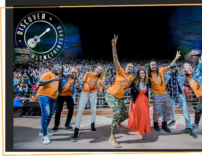 Michael Franti on stage with friends in orange shirts, peace signs up