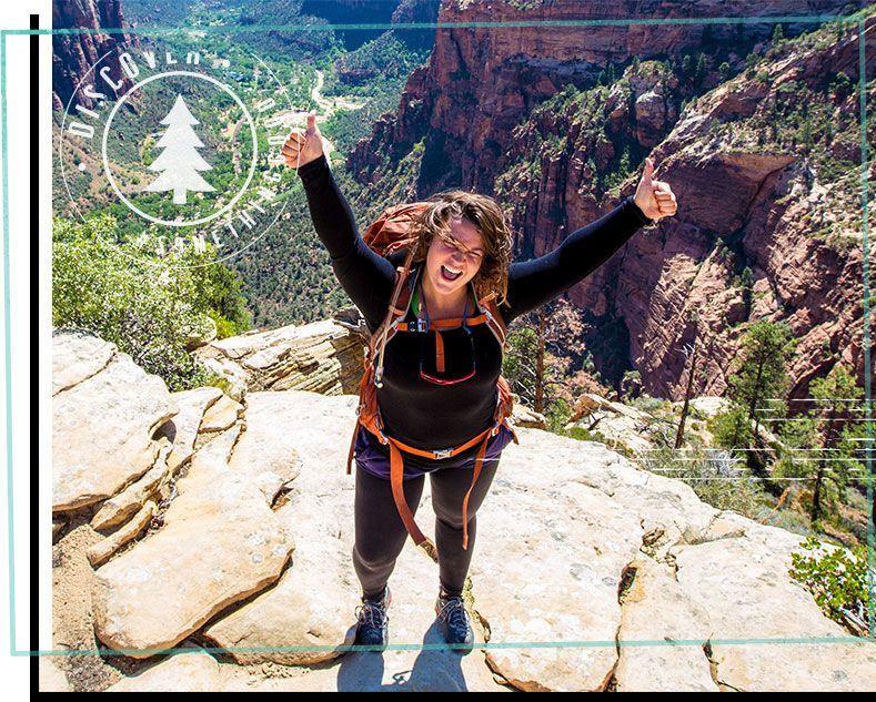 young woman hiker posing on top of a cliff in Montana with her hiking backpack and two thumbs up