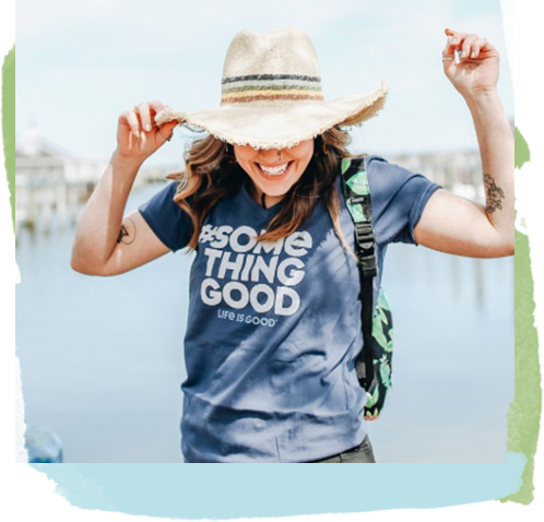 Woman wearing a hat, backpack and special edition something good tee